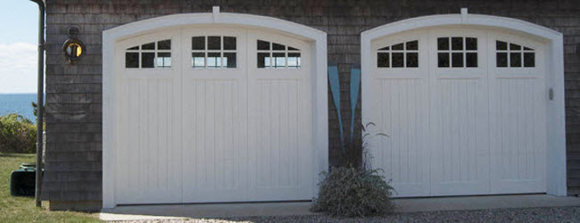 white arched wood garage doors with windows