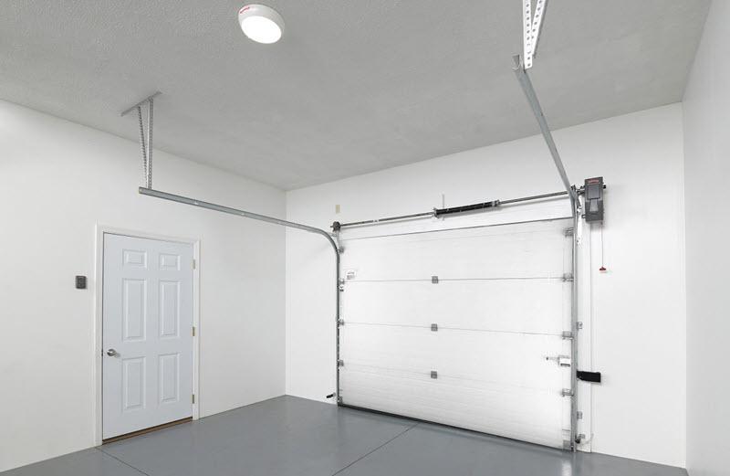 clean garage with white garage door and white entry door